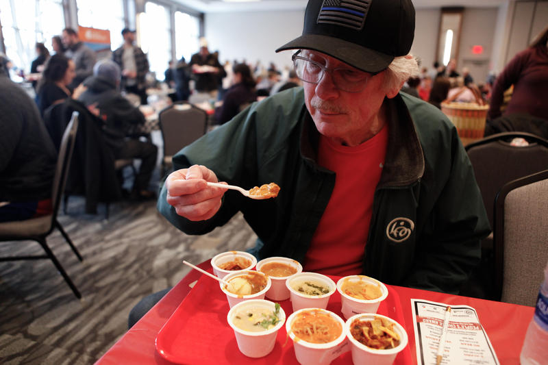 Dave Mertz reaches for a spoonful of chili during The Downtown Chili Cook-Off at the Park Place Hotel.