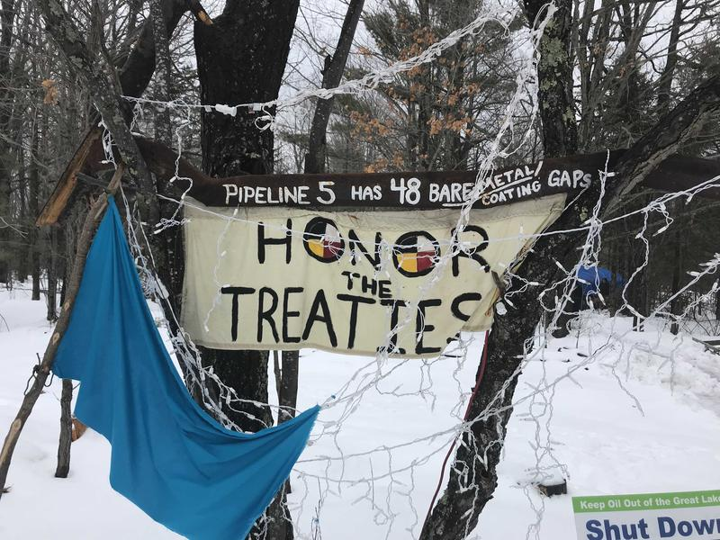 "A sign that says ""Honor the Treaties"" hangs between two trees against a snowy landscape."