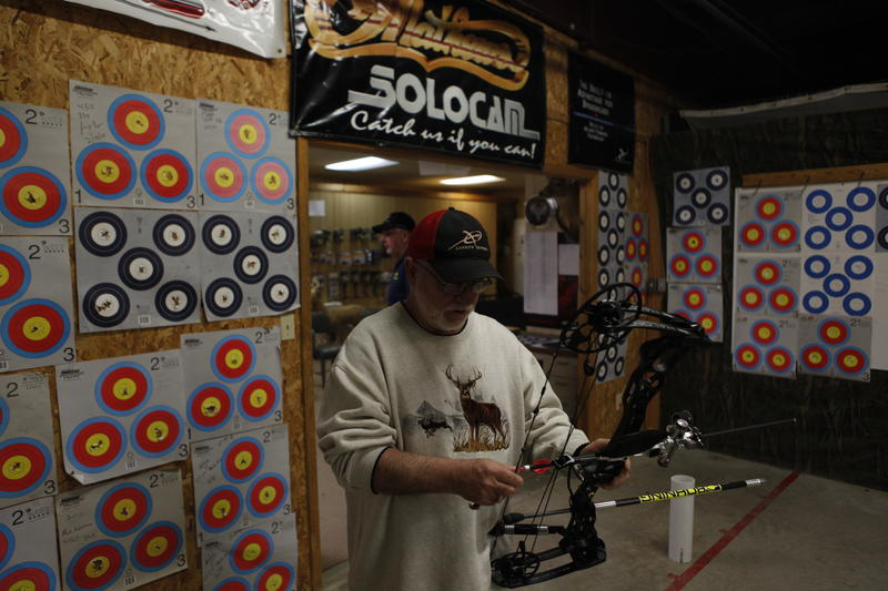Larry Martin puts another arrow on his bow string at FPS Archery shop in Cadillac.