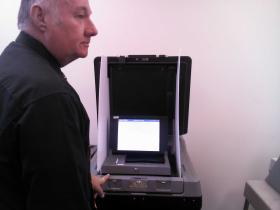 Mike Hoppenrath, city clerk of Watertown, inspects one of the new voting machines.