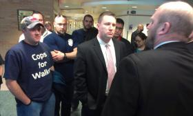 Milwaukee Police and Firefighters confront Milwaukee Aldermen outside a public hearing of the legislature's budget committee.  The Aldermen testified against a provision that would end Milwaukee's longstanding residency requirement for municipal workers.