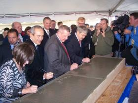The dignitaries sign their names to commemorate the event.