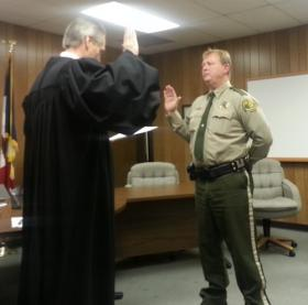 Judge Michael Schilling (L) administers the Oath of Office to Sheriff Jim Sholl
