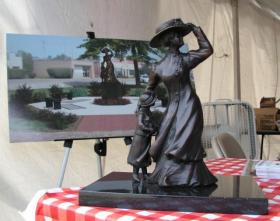 A statuette of the memorial, with an artist's rendition in the background.