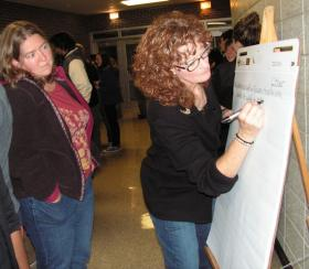 Erin Easterling (left) looks on as her idea is added to one of the lists.