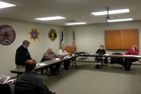 AMJET CEO Paul Roos (standing) addresses members of the Lee County Board of Supervisors