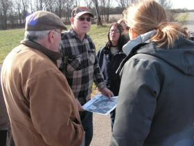 Joe Cooper shows a tour group a map of the proposed North Canton Mine.