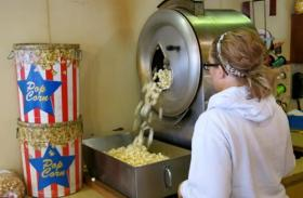 A Del's Popcorn shop employee in Decatur starts the vintage popcorn popper. Del's relies heavily on holiday sales, but is struggling with the high price of popcorn.