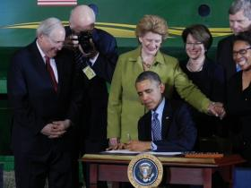 President Obama signs the Agriculture Act of 2014 as members of Congress and the Cabinet look on.