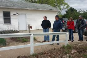Conservation Director Tom Buckley (2nd Left) shows the damage to the Conservation Board's office from an indirect lightning strike.