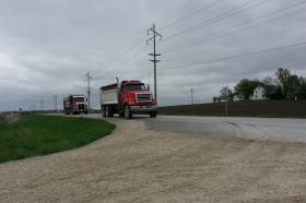 Two trucks prepare to turn onto 320th Avenue on Tuesday, May 13, 2014.