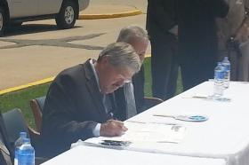 Governor Terry Branstad re-enacts the signing of the legislation approving a loan for Keokuk Area Hospital into law.