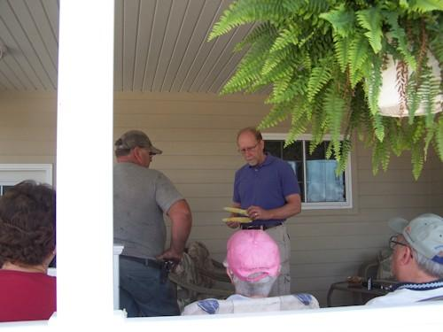 Rep. Loebsack examines two underdeveloped ears of corn while talking to farmers at the home of Steve Newberry.