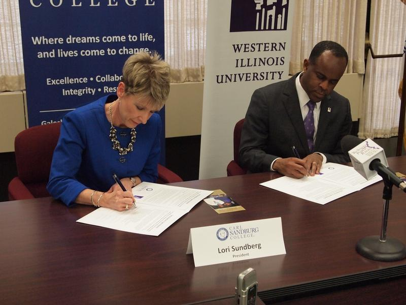 Presidents Lori Sundberg of Carl Sandburg College and Jack Thomas of Western Illinois University sign an agreement on a new program for honor students in Galesburg.