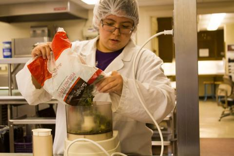 Iowa State University food science major Erika Orejola grinds frozen poblano peppers as her group prepares their commercial-scale quantity of Abrasa hot sauce.