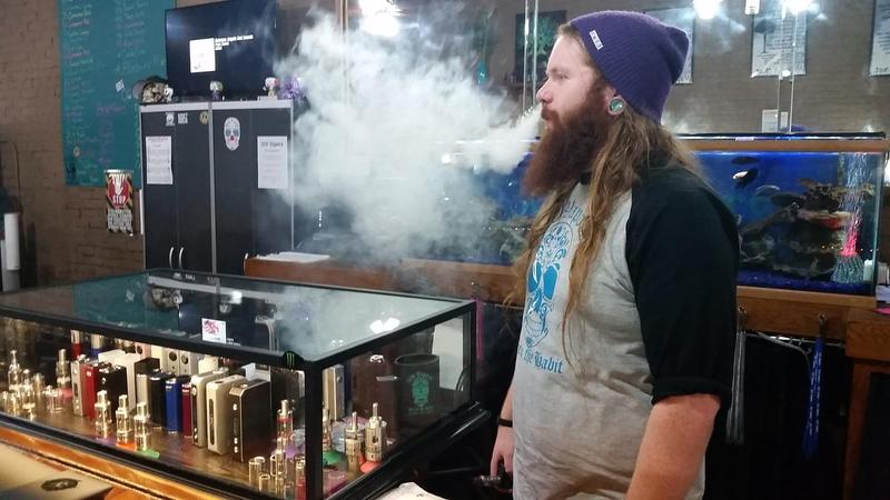 22-year-old Christian Justus smokes an e-cigarette at 309 Vapors in Macomb. He is the shop's manager.