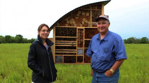 Researchers Daphne Mayes (left) and Scott Campbell stand in front of the bee hotel in Lawrence, Kan.
