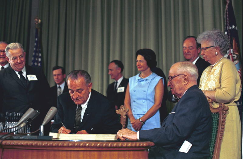President Johnson signed Medicare into law on July 30, 1965.  Former President Harry S Truman is seated to the right.