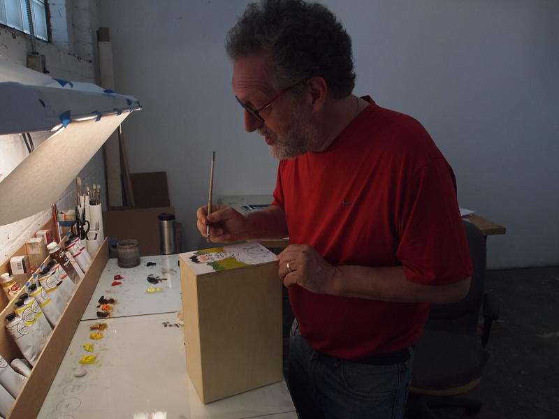 John Bakker works on painting one of the 300 boxes he has planned for the Galesburg Portrait Project.
