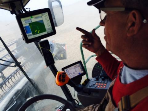 Blake Hurst, president of the Missouri Farm Bureau, in the cab of his combine, harvesting soybeans on his family's northern Missouri farm. He's watching satellite monitors that show yields, moisture content and fertilizer use.