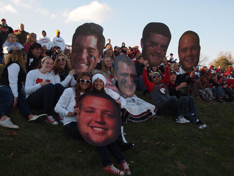 Monmouth College fans cheer on their team with large cutouts of players on the team.