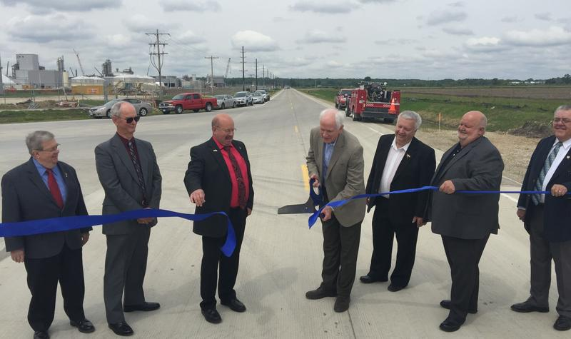 IFC President Larry Holley cuts the ribbon marking the official opening of 360th Avenue along the eastern edge of the plant. He was joined by county, state and economic development leaders from southeast Iowa.