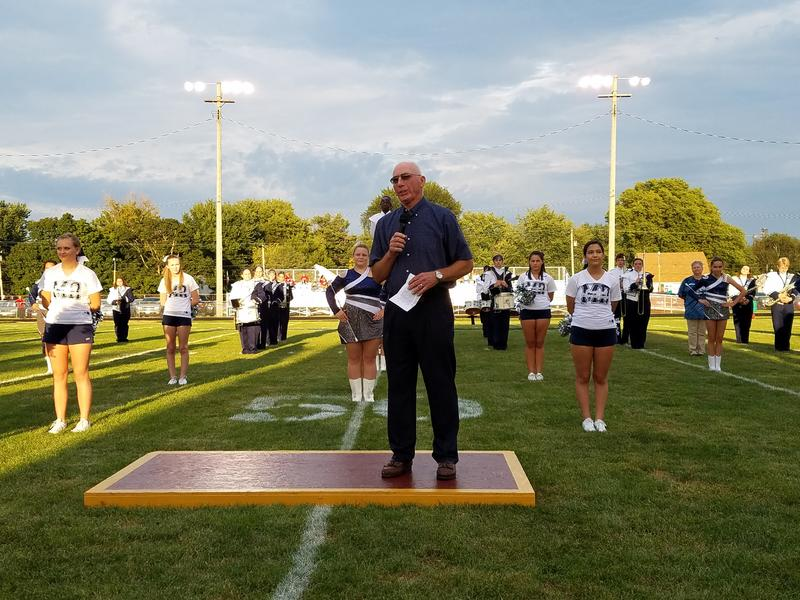 Warren Dobry speaks to the crowd Friday night in Monmouth on the field named after him.  The Monmouth-Roseville High School band and cheerleaders stand behind him.