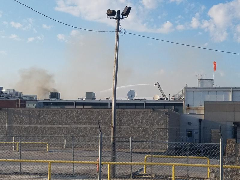 Firefighters on aerial ladders battle the blaze on the north side of the Smithfield Foods plant in Monmouth Monday afternoon.