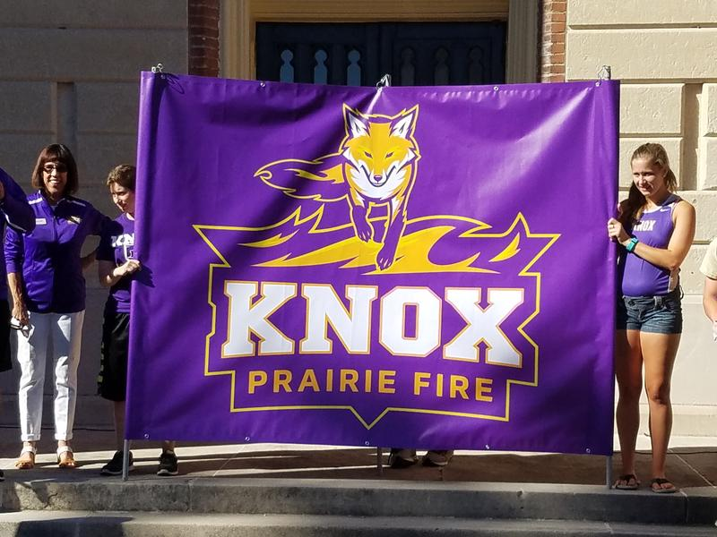 Knox College President Teresa Amott (left) stands to the side as two Prairie Fire student athletes reveal a fox as the new mascot for the school.