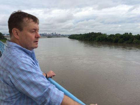 David Greene, Kansas City Water Services laboratory manager, stands on a platform of the intake facility above the Missouri River on the Missouri side. Kansas City's downtown can be seen in the distance.