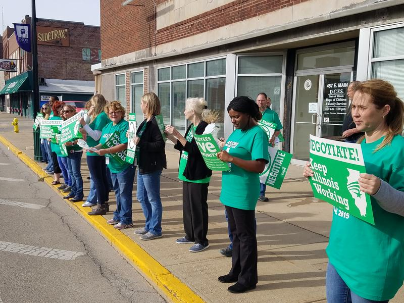 Around 20 union members stand along East Main Street in Galesburg to rally support.  They want Governor Bruce Rauner to come back to the bargaining table.