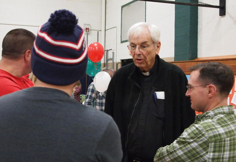 Monsignor Richard Pricco talks with parishioners during his farewell spaghetti supper at St. Paul Catholic Church in Macomb