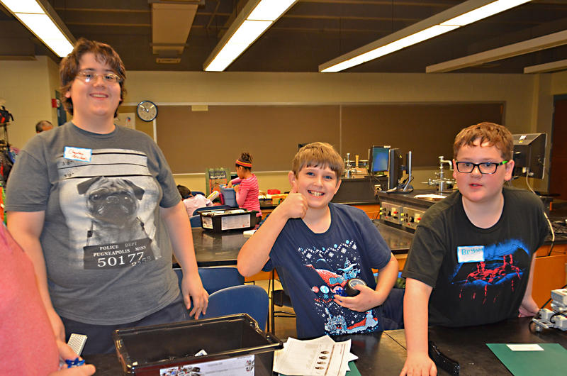 Charley, Kadin, and Bryant taking a break from working on their robot to pose for a photo.