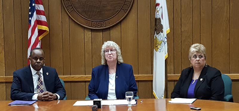 WIU President Jack Thomas, BoT Chair Cathy Early, and Interim Provost Kathy Neumann (left to right) during the June 28 news conference.  Early's term as Chair has since expired.  The new BoT Chair is Carolyn Ehlert Fuller.