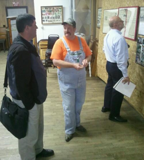 Mayor Tom Allen (middle) speaks with Bruce Hudson with RUSS while journalist Curt Swarm looks at pictures of Mount Sterling's History.