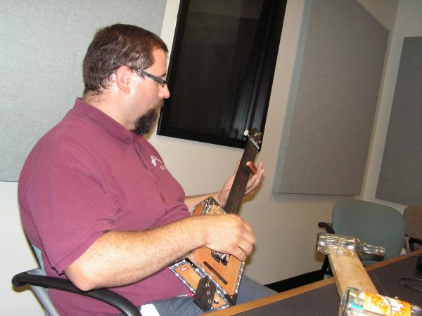 Draws playing a cigar box guitar during an interview in the Tri States Public Radio news studio.
