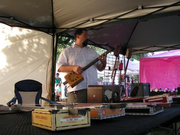 John Draws sold cigar box guitars from a booth during Heritage Days in Macomb. He'll also sell them July 18 & 19 during the Spring Lake Bluegrass Jam & Festival at Spring Lake Park in Macomb.