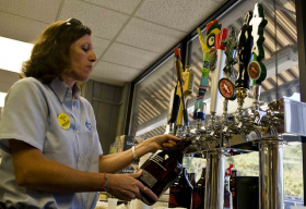 A liquor store employee fills a 64 oz, or half-gallon, growler in South Carolina. Sale of the size is currently prohibited in Florida.
