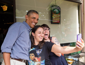 President Barack Obama poses for a photo outside Magnolia's Deli & Café during the college affordability bus tour, in Rochester, N.Y., Aug. 22, 2013