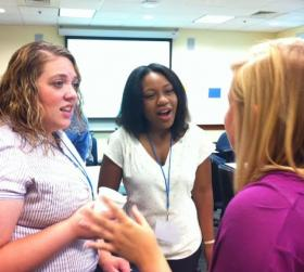 (From left) New residents Kylee Griffin, Tiffany Allen, and Chelsea Steiner talk at Jacksonville Teacher Residency Program orientation at UNF.