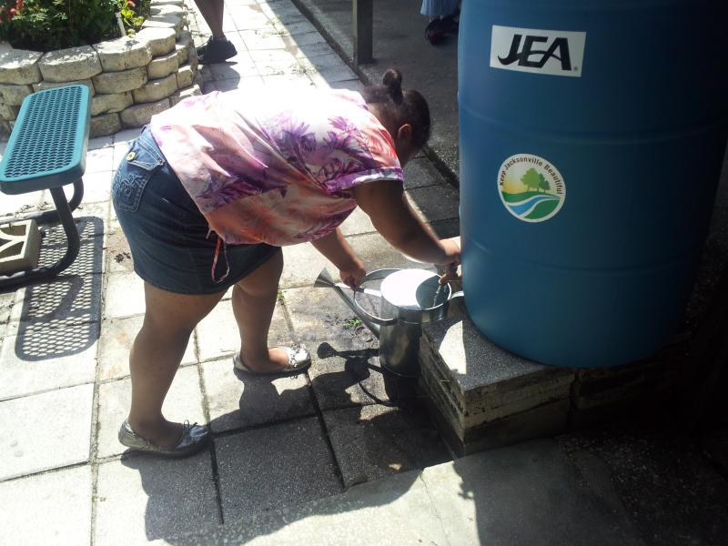A student pours water into a watering can