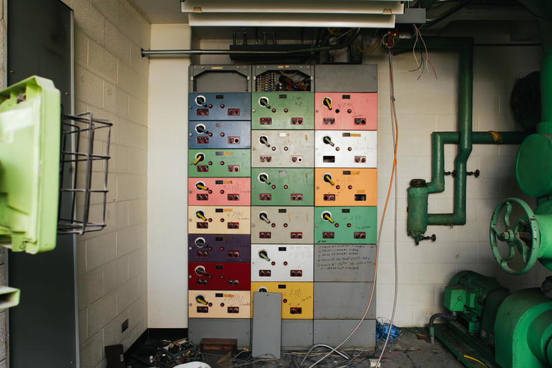 An additional array of switches is located on the wall behind the control panel.