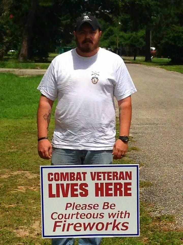 U.S. Army Staff Sergeant (Ret.) Jon Dykes stands in his Pace, Florida yard with the sign he created.