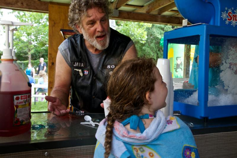 Java, a member of the Seven Bridges Chapter of Bikers Against Child Abuse (BACA), serves snow cones at Kids Day at the Fleet Reserve Association in Orange Park, Fla. on July 26, 2014.