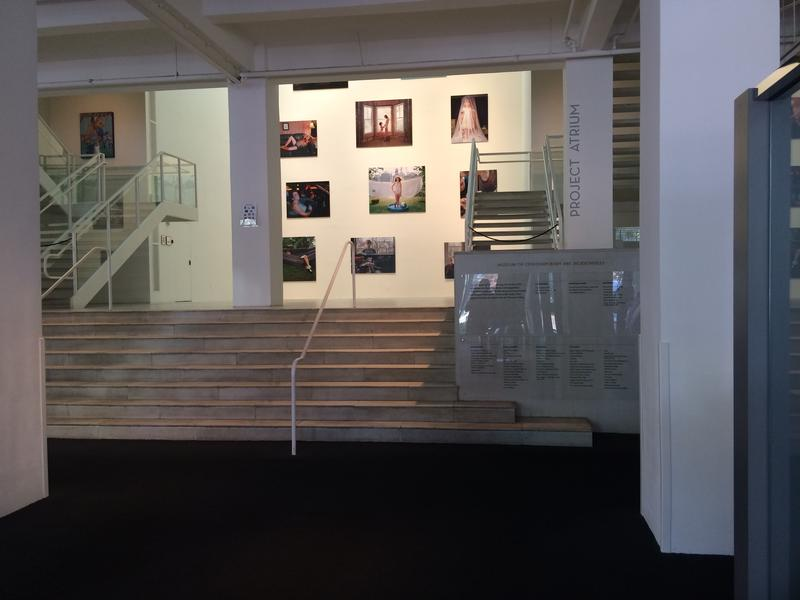 """The view of the photograph """"Janine Eight Months Pregnant"""" by artist Angela Strassheim from outside Café Nola. The photograph is at the bottom right corner, mostly covered by the staircase."""