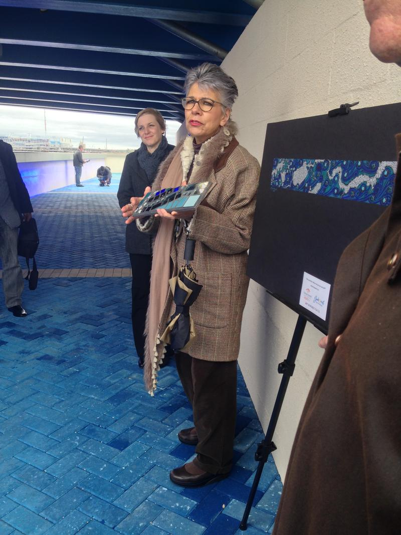 Kate Garcia Roux shows a depiction of the mural that will adorn the Riverwalk wall.