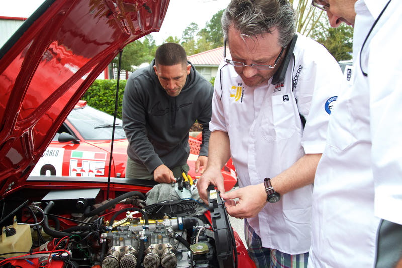 John Campion (center) sorts out some last minute hiccups with the rally cars.