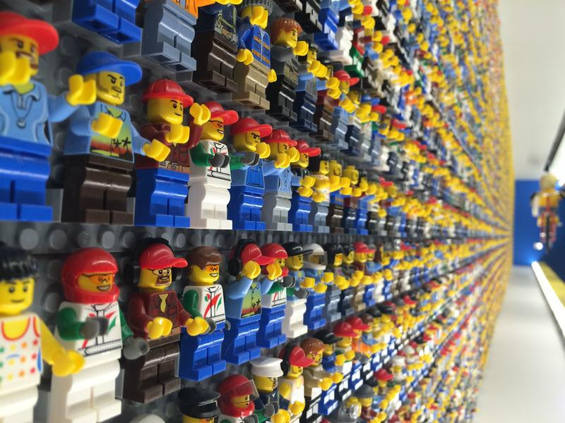 The wall behind the check-in counter is covered with LEGO Minifigures.
