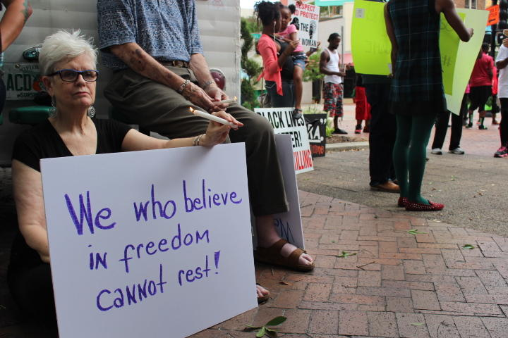 "A woman sits next to a trailer in Hemming Park during the vigil for Sandra Bland with a sign that reads, ""We who believe in freedom cannot rest!"""