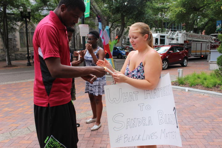 Vigil attendees light candles in memory of Sandra Bland